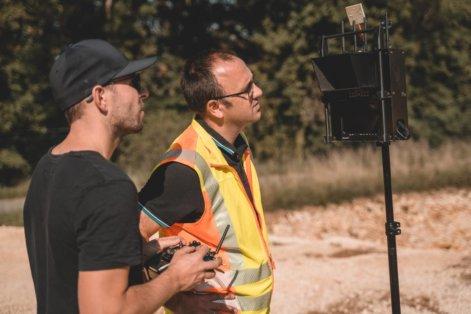 Monitor-Drohne-Kamera-Pilot-und-Kunde-Graupner-Sender-Digitales-3D-Aufmaß-per-Drohne-Steinbruch-Vermessung-Foerderband-Aushub